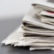 A closeup shot of several newspapers stacked on top of each other
